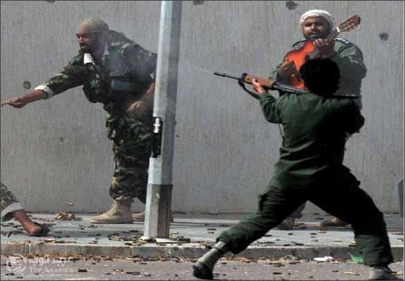 صور مقاتل من ثوار ليبيا يعزف على الجيتار في قلب معركة سرت في ليبيا