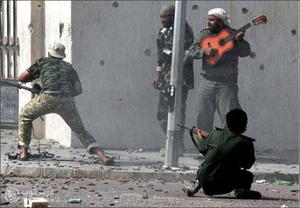 صور مقاتل من ثوار ليبيا يعزف على الجيتار في قلب معركة سرت في ليبيا صحيحة