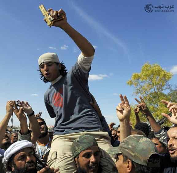صورة الشاب البطل أحمد الشيباني قاتل معمر القذافي و هو محمول فوق رؤوس الثوار وهو يحمل مسدس معمر القذافي الذهبي !